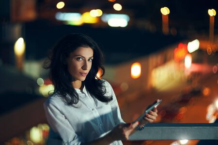 Young woman holding a digital tablet in hands texting at night with city lights on background