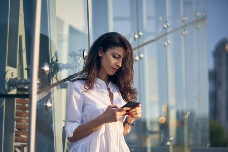 Portrait of young business woman over office buildings holding a smart phone in a hand texting Imagens
