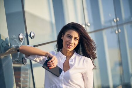 Young business woman with phone in hand, standing leaning on modern glass structure of office building looking at camera smiling