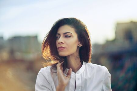 Portrait of young woman over cityscape golden sunset
