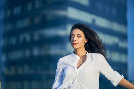 Young business woman over modern glass structure of office building looking to the side