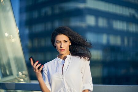 Young business woman with phone in hand, standing over on modern glass structure of office building looking to the side thinking Imagens