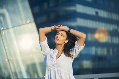 Young business woman over modern glass structure of office building enjoying with closed eyes