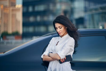 Smiling business woman standing outdoors leaning on the car with modern glass office buildings at background looking down