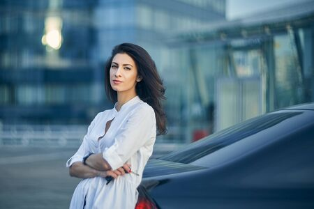 Young business woman standing outdoors leaning at the car with modern glass structure of office buildings at background