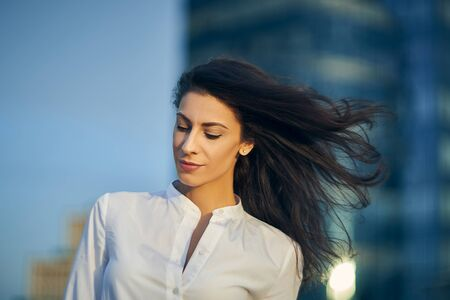 Young business woman with flying hair over modern glass structure of office building