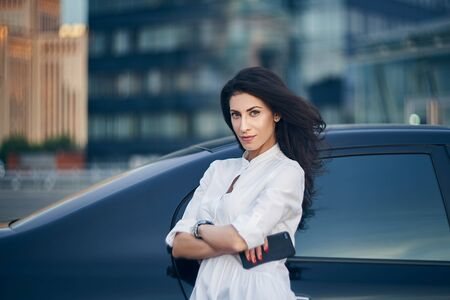 Business woman standing outdoors leaning on the car with modern glass office buildings at background