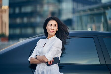 Business woman standing outdoors leaning on the car with modern glass office buildings at background looking to side