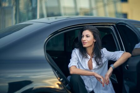 Smiling business woman sitting in the car with modern office buildings at background Imagens