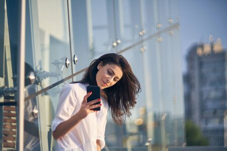 Young beautiful woman making self portrait with her smart phone over modern glass structure of office building Imagens