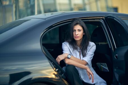 Serious business woman sitting in the car with modern office buildings at background