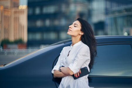 Young business woman standing outdoors leaning on the car with modern glass office buildings at background relaxing with closed eyes