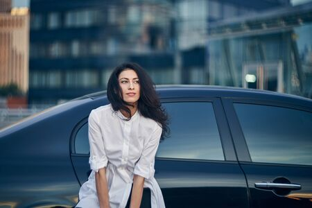 Smiling business woman standing outdoors leaning on the car with modern glass office facades at background Imagens