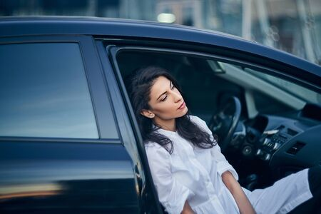 Young business woman sitting in the car on passenger seat, with opened door, relaxing