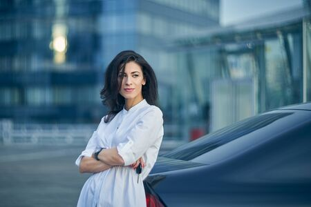 Smiling business woman standing outdoors leaning on the car with modern glass structure of office buildings at background Banque d'images