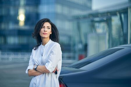 Pensive business woman standing outdoors leaning on the car with modern glass structure of office buildings at background