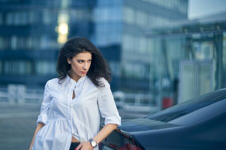 Seious business woman standing outdoors leaning on the car with modern glass structure of office buildings at background Imagens