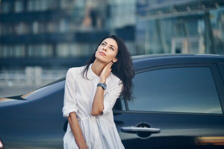 Pensive business woman standing outdoors leaning on the car with modern glass office buildings at background looking up Imagens