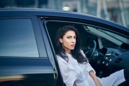 Young business woman sitting in the car on passenger seat, with opened door Imagens