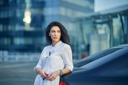 Young business woman standing outdoors leaning on the car with modern glass structure of office buildings at background Imagens