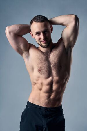 Muscular shirtless man posing with hands over head, looking at camera Imagens
