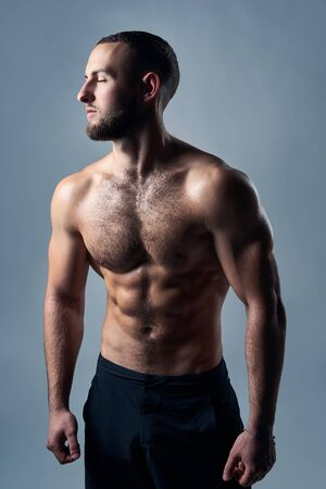 Muscular shirtless man with hands over back, standing with closed eyes