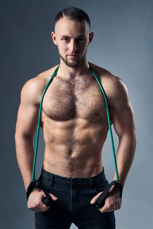 Muscular shirtless man standing with expander over shoulders, looking at camera with intense look Imagens