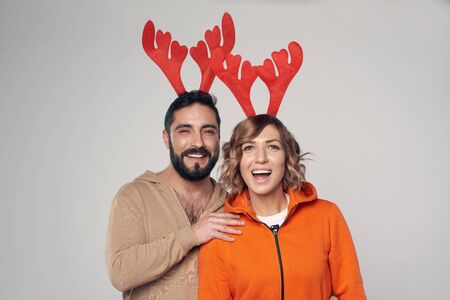 Winter holidays. Happy smiling couple wearing christmas deer costumes looking at camera smiling