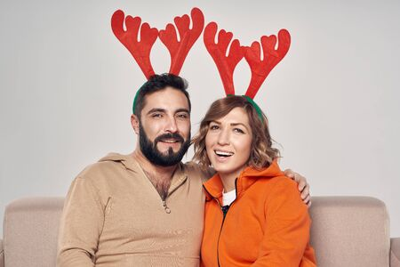 Winter holidays. Happy smiling couple sitting on sofa wearing christmas deer costumes looking at camera smiling