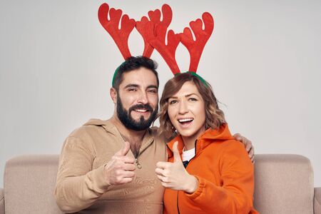 Winter holidays. Happy smiling couple sitting on sofa wearing christmas deer costumes looking at camera smiling and giving thumb up