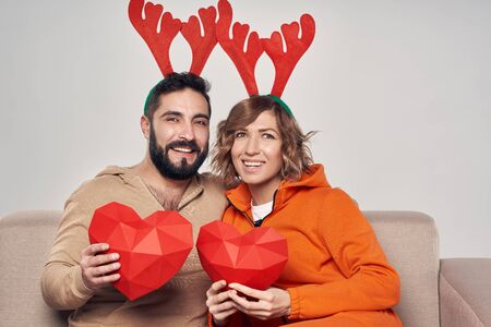 Winter holidays. Happy smiling couple sitting on sofa wearing christmas deer costumes and holding hearts in hands, looking at camera smiling