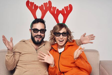 Christmas entertainment. Happy surprised family wearing christmas deer costumes and 3D glasses while sitting on sofa Imagens