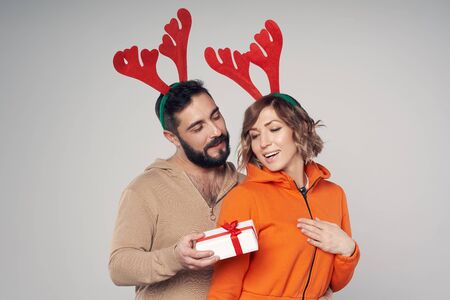Winter holidays. Happy smiling couple wearing christmas deer costumes, man giving a gift box to his woman
