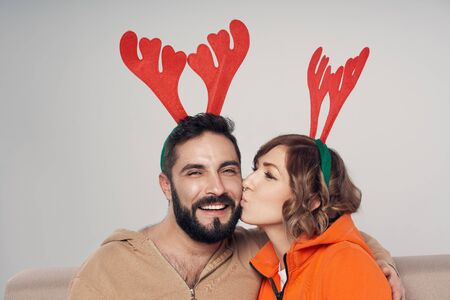 Winter holidays. Happy smiling couple wearing christmas deer costumes , woman kissing her man