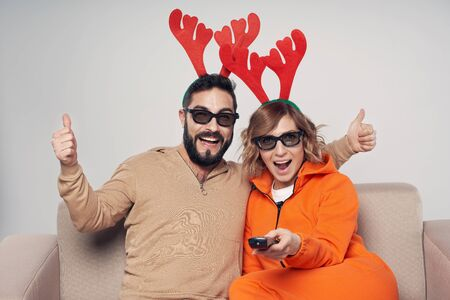 Christmas entertainment. Happy excited couple wearing christmas deer costumes and 3D glasses pointing remote control at camera, man gesturing thumb up