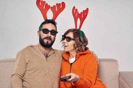 Christmas entertainment. Happy surprised family wearing christmas deer costumes and 3D glasses pointing remote control at camera Imagens