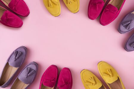 Multicolored suede moccasins shoes making a frame with copy space, over pink background, top view Imagens