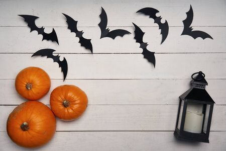 Halloween card. Pumpkins, black paper decoration bats and black lantern on white wooden planks, with blank copy space in center