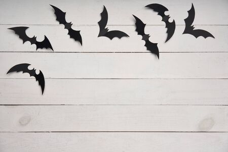 Halloween card. Black paper bats flying over white wooden planks, with blank copy space