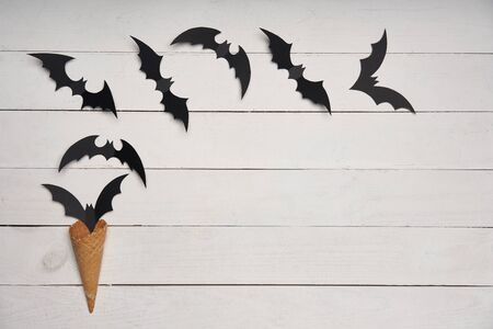Halloween card. Black paper bats flying out of waffle cone over white wooden planks, with blank copy space