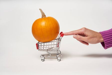 Woman's hand pulling a small shopping cart with orange pumpkin in it on white background