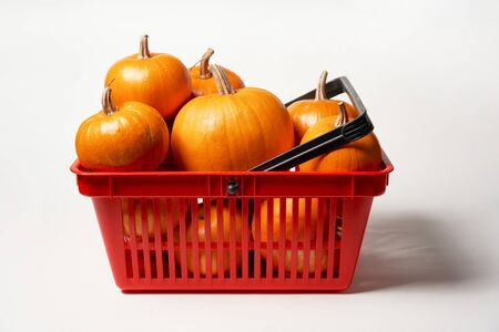 Ripe orange pumpkins in shopping basket on white background