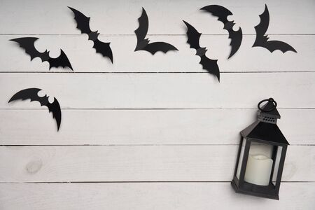 Halloween card. Black paper decoration bats and black lantern on white wooden planks, with blank copy space in center