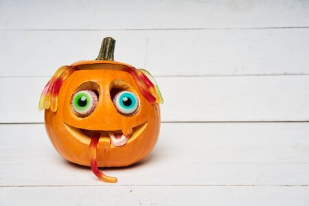 Kind smiling Halloween Pumpkin with candy eyes, teeth and hair of gelatin worms over white wooden planks