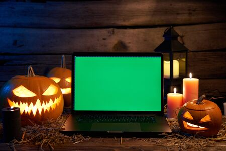Jack O Lantern Halloween pumpkins on rough wooden planks with candles glowing in the dark with opened laptop with green screen empty space