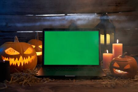 Jack O Lantern Halloween pumpkins on rough wooden planks with candles with opened laptop with green screen with the light leaking between plank chinks Imagens