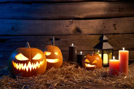 Jack-O-Lantern Halloween pumpkins on rough wooden planks with candles glowing in the dark