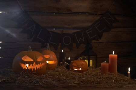 Jack-O-Lantern Halloween pumpkins on rough wooden planks with candles glowing in the smoky dark with the light leaking between plank chinks