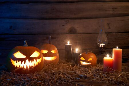 Jack-O-Lantern Halloween pumpkins on rough wooden planks with candles and kerosene oil lantern brass lamp glowing in dark with blue backlight