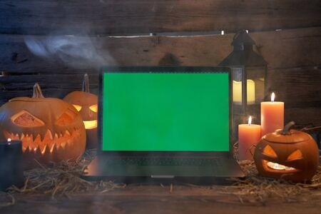 Jack-O-Lantern Halloween pumpkins on rough wooden planks with candles with opened laptop with green screen with the light leaking between plank chinks